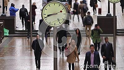 Lasso di tempo dei pendolari che camminano dopo gli orologi, Canary Wharf, Londra video d archivio