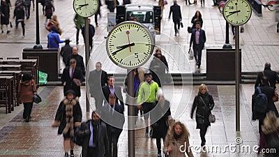 Lasso di tempo dei pendolari che camminano dopo gli orologi, Canary Wharf, Londra archivi video