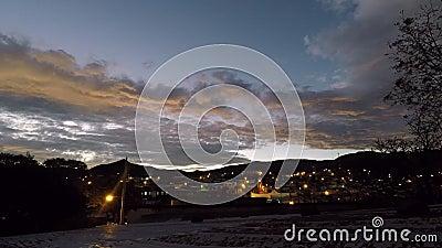 Lasso di tempo - tramonto nuvoloso sull'orlo di una cittadina stock footage