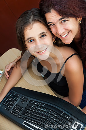 Latin girl and her mother working on a computer