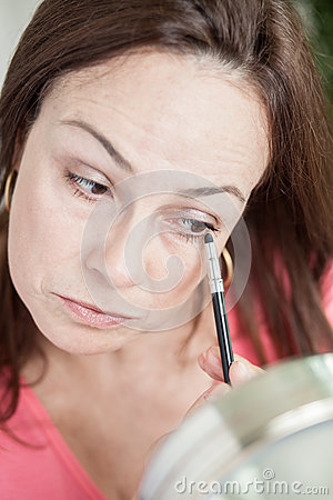 Latin woman using make up