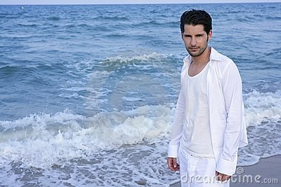 Latin young man white shirt walking blue beach