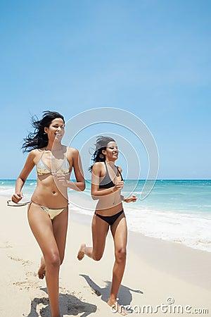 Latina sisters in bikini on beach