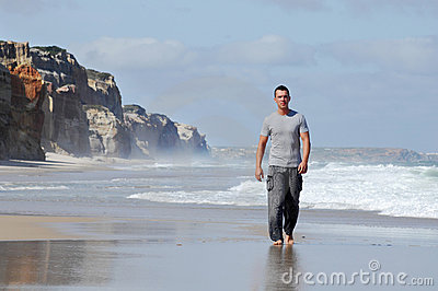 Latino man walking on a beach