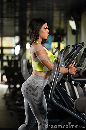 latino women on elliptical treadmill in fitness gym stock