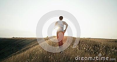 Laufender Läufermann, der bei Sonnenuntergang rüttelt Männliches Rüttlertraining für Marathon lässt Betrieb herauf Hügel im Schat stock video