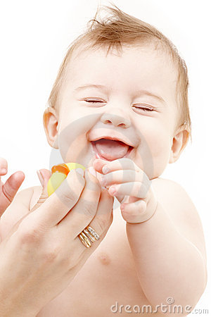 Laughing baby boy in mother hands with rubber duck