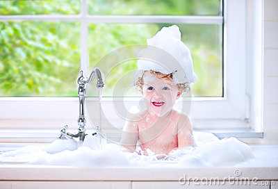 Laughing baby girl playing in big kitchen sink with foam