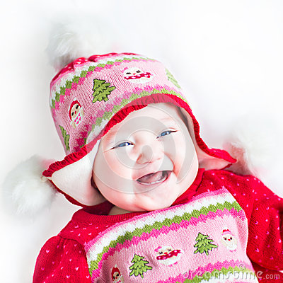 Laughing baby girl in a red dress with Christmas ornament