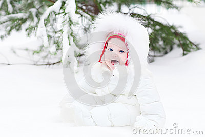 Laughing baby sitting in snow under a Christmas tree