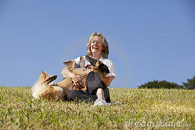 Laughing beautiful woman playing with her dog