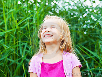 Laughing blonde little in summer