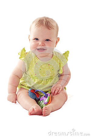 Laughing blue eyed baby sits with her toy rattle.