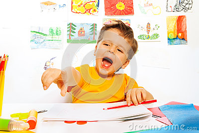 Laughing boy drawing with pencil on the paper