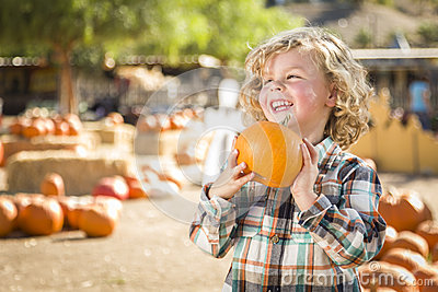 Laughing Boy Holding His Pumpkin at a Pumpkin Patch