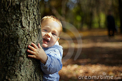 Laughing boy peeking from behind a tree