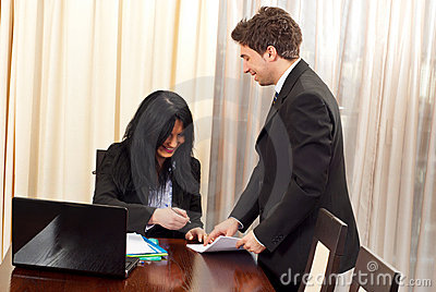 Laughing business people signing papers