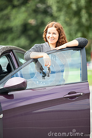 Laughing cheerful woman standing near new car