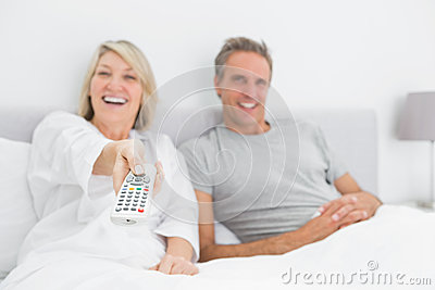Laughing couple watching tv in bed