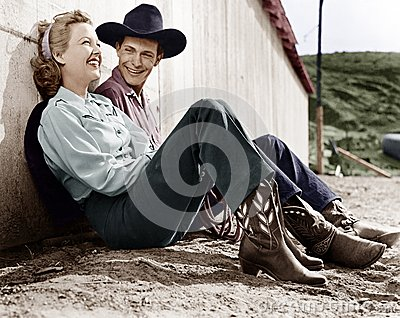 Laughing couple in western attire sitting on the ground Stock Photo