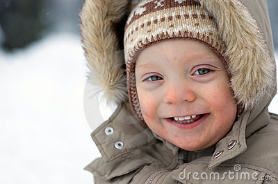 Laughing cute baby boy winter snow