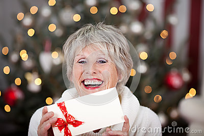 Laughing elderly lady with an Xmas gift voucher