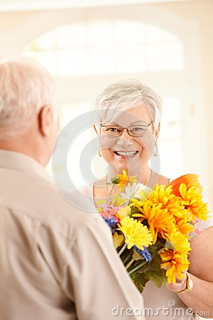 Laughing elderly woman getting bouquet