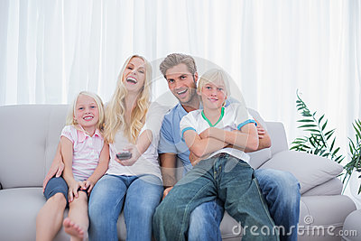 Laughing family watching TV together