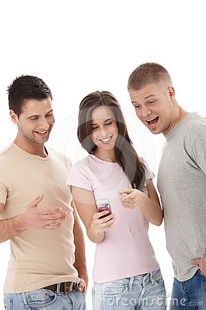 Laughing friends looking at mobile phone