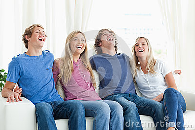 Laughing friends sit on the couch together