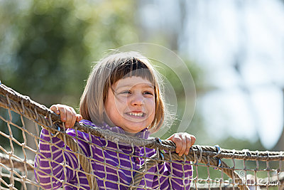 Laughing girl climbing on ropes Stock Photo