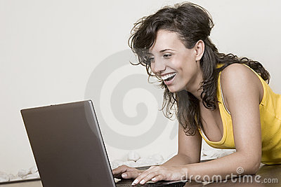 Laughing girl with the laptop lying on the floor