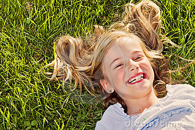 Laughing girl lying in grass