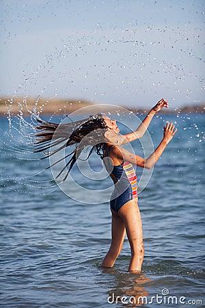Laughing girl throws her wet hair through the air