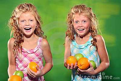 Laughing girls holding some fruit