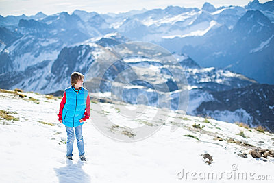 Laughing happy boy in snow on top of mountain