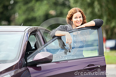 Laughing happy woman standing near new car