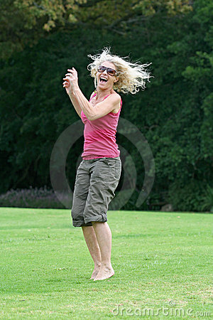 Laughing and jumping, healthy woman enjoying herself!