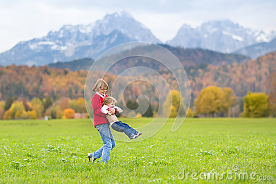 Laughing kids in field between snow mountains