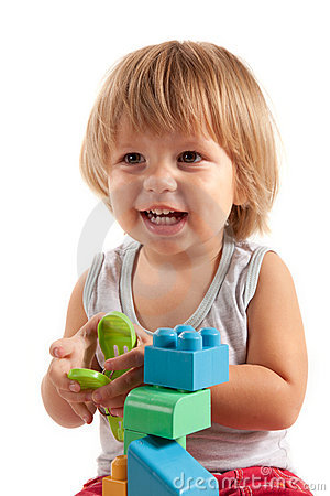Laughing little boy playing with blocks