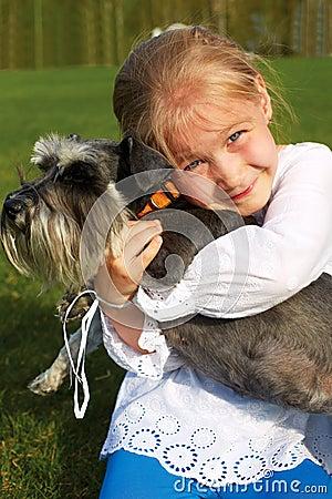 Laughing little girl hugging her dog