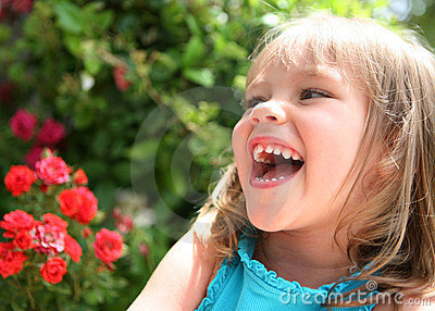 Laughing little girl near red flowers