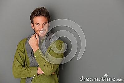 Laughing man posing at wall