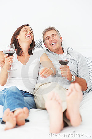 Laughing mature couple lying on their bed