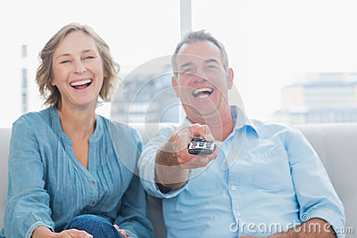 Laughing middle aged couple sitting on the couch watching tv