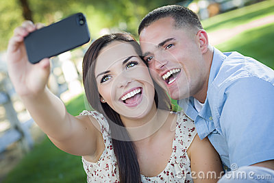 Laughing Mixed Race Couple Taking Self Portrait in Park