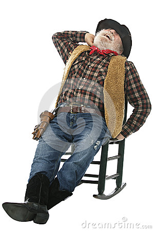Laughing old cowboy stretches in rocking chair