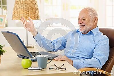 Laughing old man using laptop