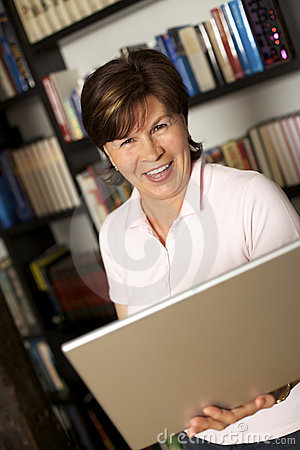 Laughing senior woman standing with laptop