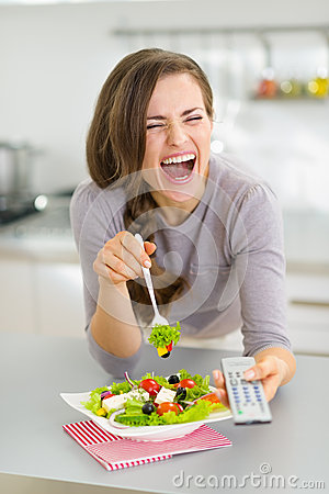 Laughing woman eating salad and watching tv